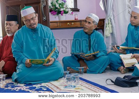 Labuan,Malaysia-Aug 30,2017:Muslim men perform Quran recitation during Aqiqah ceremony in Labuan,Malaysia.Islamic traditions after a baby is born include shaving his head & sacrificing an animal