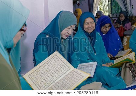 Labuan,Malaysia-Aug 30,2017:Muslim woman perform Quran recitation during Aqiqah ceremony in Labuan,Malaysia.Islamic traditions after a baby is born include shaving his head & sacrificing an animal.