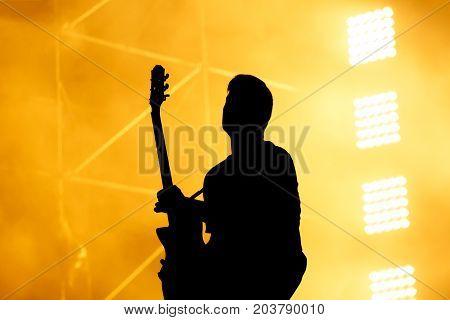 Silhouette of guitar player, guitarist perform on concert stage. Orange background, smoke, concert spotlights.