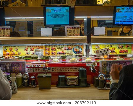 TOKYO, JAPAN -28 JUN 2017: Close up of assorted japanesse food over a table, with a screen with the menu, inside of a kaitenzushi conveyor belt sushi restaurant in Tokyo, Japan.