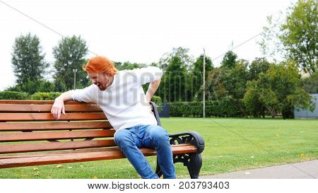 Tired Man With Back Pain, Spinal Pain, Sitting On Bench, Red Beard And Hairs