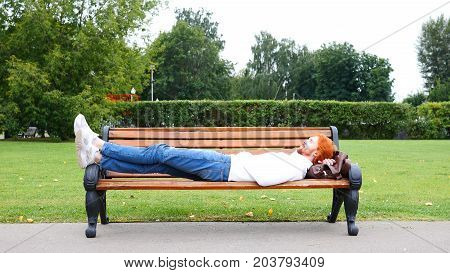Sleeping Tired Man With Red Beard And Hairs In Park On Bench