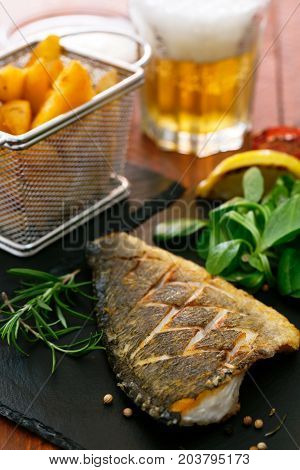 Baked dorado with fresh salad, vegetables and potato chips. Served with fresh beer in glass