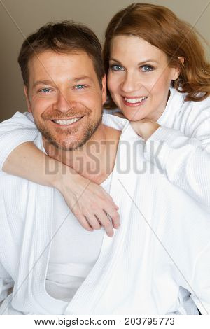 Cute couple smiling in white bath robes.
