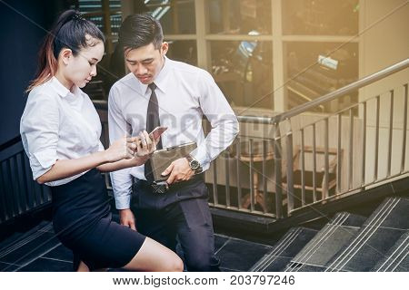 Business Man And Woman Using Smartphone Standing Talking And Viewing Documents Outdoor