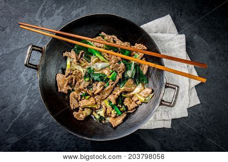 Traditional Chinese Mongolian Beef Stir Fry In Chinese Cast Iron Wok With Cooking Chopsticks, Stone