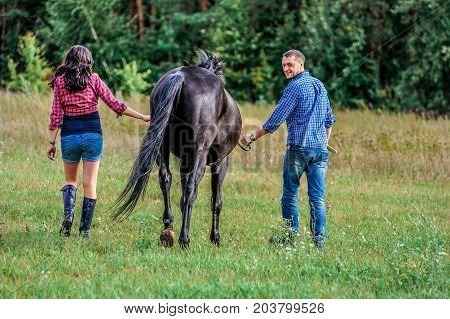 Awaiting The Child, Walking On The Meadow. Young Couple - She Is A Handsome Brunette With Long Hair,