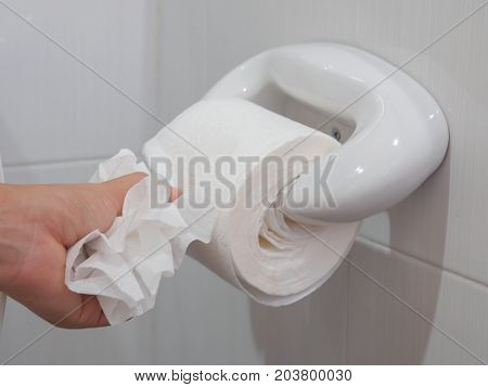 Soft focus female hand picking a white tissue from tissue roll in the restroom.
