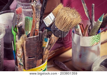 On the table in the glass are a lot of artist's brushes of different sizes pencils and other drawing tools the old working table of the artist