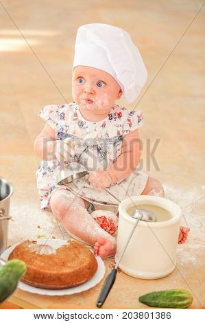 A little toddler girl in chef's hat sitting on the kitchen floor soiled with flour playing with food making mess and having fun