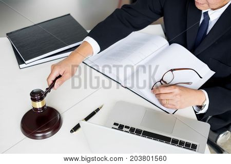 Male Judge lawyer In A Courtroom Striking The Gavel on sounding block.