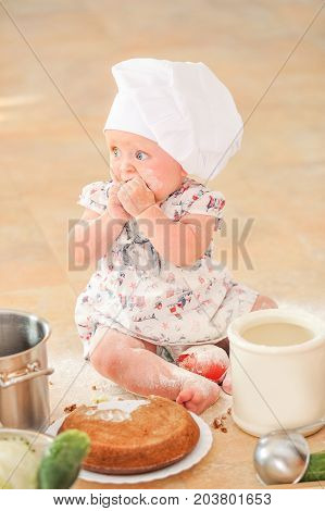 A little girl in chef's hat sitting on the kitchen floor soiled with flour playing with food making mess all around