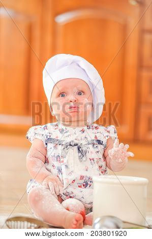Toddler-girl in chef's hat sitting on the kitchen floor soiled with flour playing with food making mess and having fun
