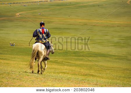 Mongolian Man Traditional Riding Horse Downhill