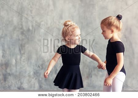 Two small fair-haired girls ballerinas in black packs white pantyhose white pointe shoes learn to dance a Russian ballet in a black dance studio