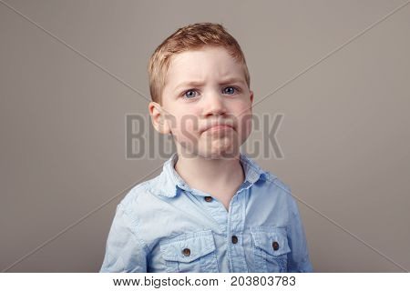 Closeup portrait of cute adorable blond redhead Caucasian little boy in blue shirt standing in studio on light white background. Child kid looking in camera with funny sceptical face expression