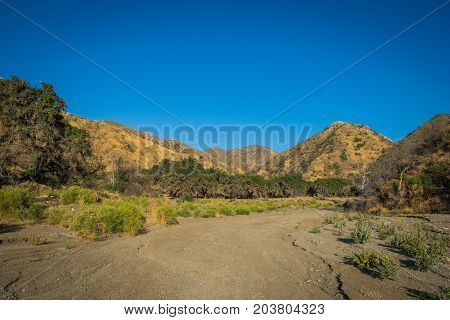 Sandy bottom of a dry riverbed wash in the mountains of southern California.