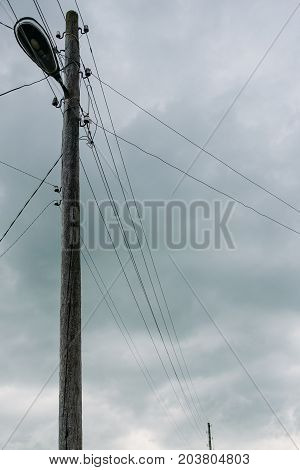 village wooden street lamp post with lantern and wires on clouds background