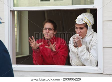 Two Women Discuss Construction Details While Standing In Window Frame For Habitat For Humanity