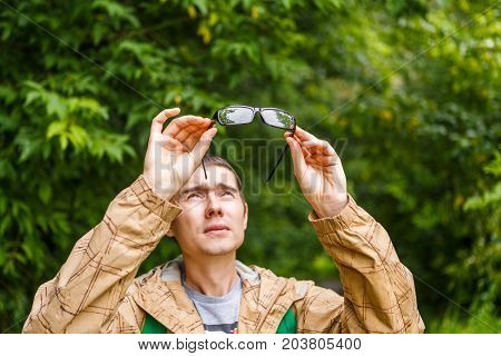 Image of man holding glasses over head against background of trees