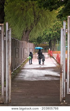 Mother is taking her children to the school on a rainy day in Tallinn Estonia. They have just gone through the steel gate of the sports field.