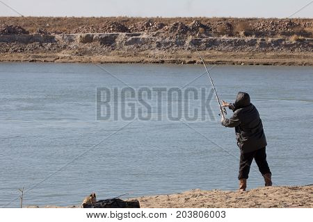fisherman catching a fish on a fishing tackle in the river