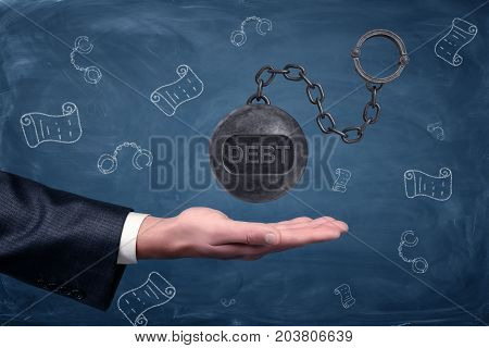 A businessman's hand turned palm up under a large hovering iron ball with a word DEBT written on it. Credit and loan. Legal prosecution. Debt collectors.
