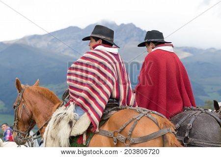 June 3 2017 Machachi Ecuador: closeup of indigenous quechua cowboys on horseback dressed traditionally in colorful poncho with mountains in the background
