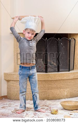 A cute preschool boy in chef's hat near the fireplace standing on the floor soiled with flour, playing with food making mess and having fun