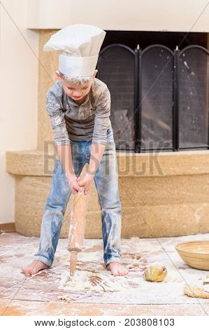 A boy in chef's hat near the fireplace standing on the floor soiled with flour playing with roller pin, making mess and having fun