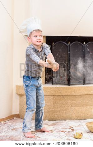 A boy in chef's hat near the fireplace dancing on floor soiled with flour playing with food making mess and having fun