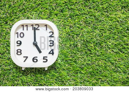 Closeup white clock for decorate in 5 o'clock on green artificial grass floor textured background with copy space