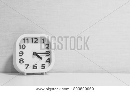 Closeup white clock for decorate show a quarter past four o'clock or 4:15 p.m. on white wood desk and cream wallpaper textured background in black and white tone with copy space