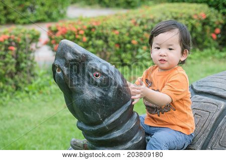 Closeup cute asian kid sit on turtle statue in the park background