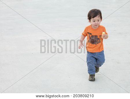 Closeup cute asian kid playing on cement floor at the car park textured background with copy space