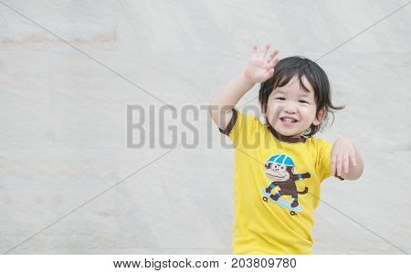Closeup enjoy asian kid with smile face on marble stone wall textured background with copy space