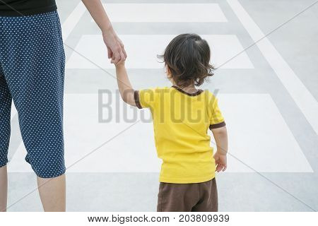 Closeup cute asian kid walk across street with his parent on the crosswalk textured background with copy space