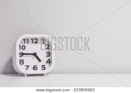 Closeup white clock for decorate show a quarter to five o'clock or 4:45 p.m. on white wood desk and cream wallpaper textured background in black and white tone with copy space