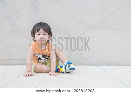 Closeup happy asian kid sit on marble stone floor and wall textured background with copy space