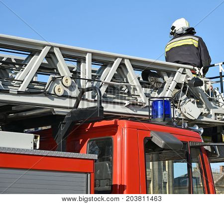 Firefighter works on the top of a fire truck