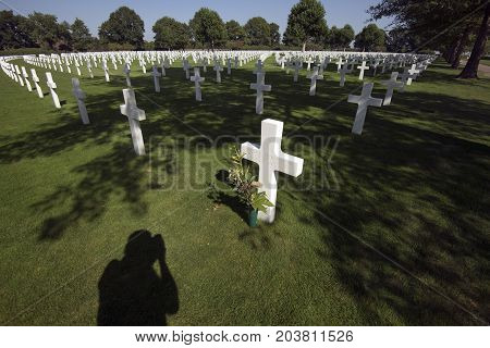 Margraten Netherlands - August 29 2017: Flowers and shadow close to graves of a fallen U.S. soldiers at the Netherlands American Cemetery and Memorial.