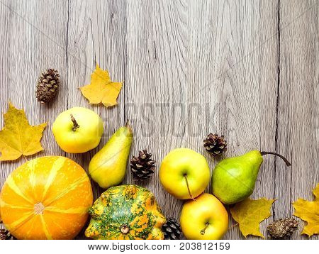 Stylish composition of colorful pumpkins autumn leaves and cones. Top view on wooden background bottom composition frame. Autumn flat lay with space for text