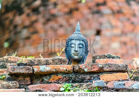 Close up metal buddha head statue on the old brick in Thailand.