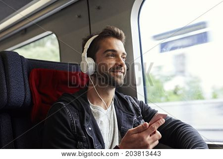 Dude on the move on train with tunes smiling