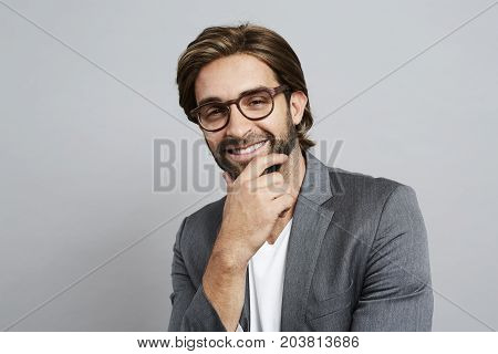 Thoughtful guy in grey suit jacket and glasses
