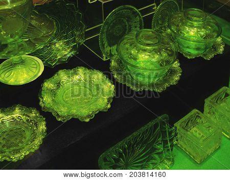 Green vintage glassware on display. Antiques glassware.