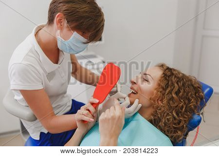 Dentist Comparing Patient's Teeth Shade With Samples For Bleaching Treatment