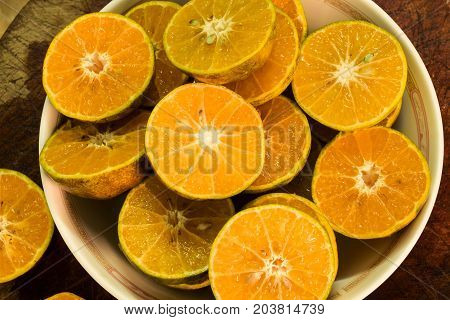 Slice fresh orange in bowl to squeeze.
