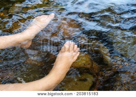 Relaxing barefoot in waterfall. Hydrotherapy from natural water resources.