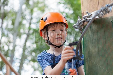 Little cute boy enjoying activity in a climbing adventure park on a summer sunny day. toddler climbing in a rope playground structure. Safe Climbing extreme sport with helmet and Carabiner. insurance